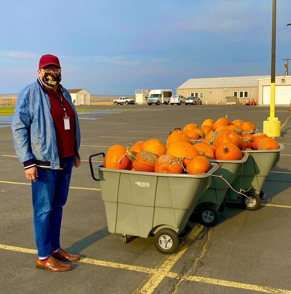 Superintendent Brown standing next to a cart of pumpkins