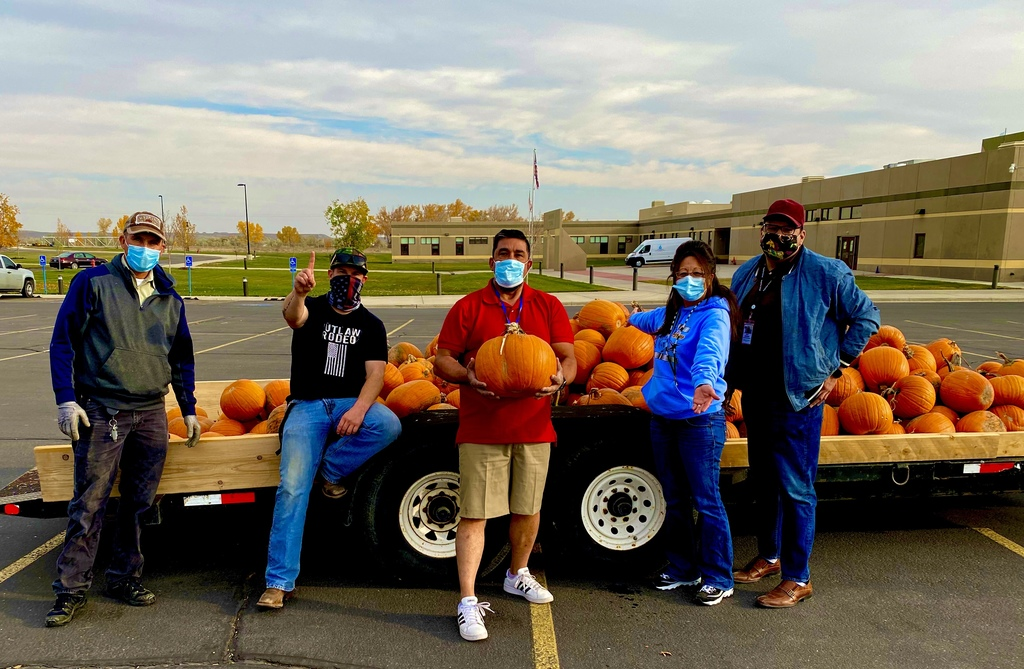 Five staff members standing in front of a trailer of pumpkins